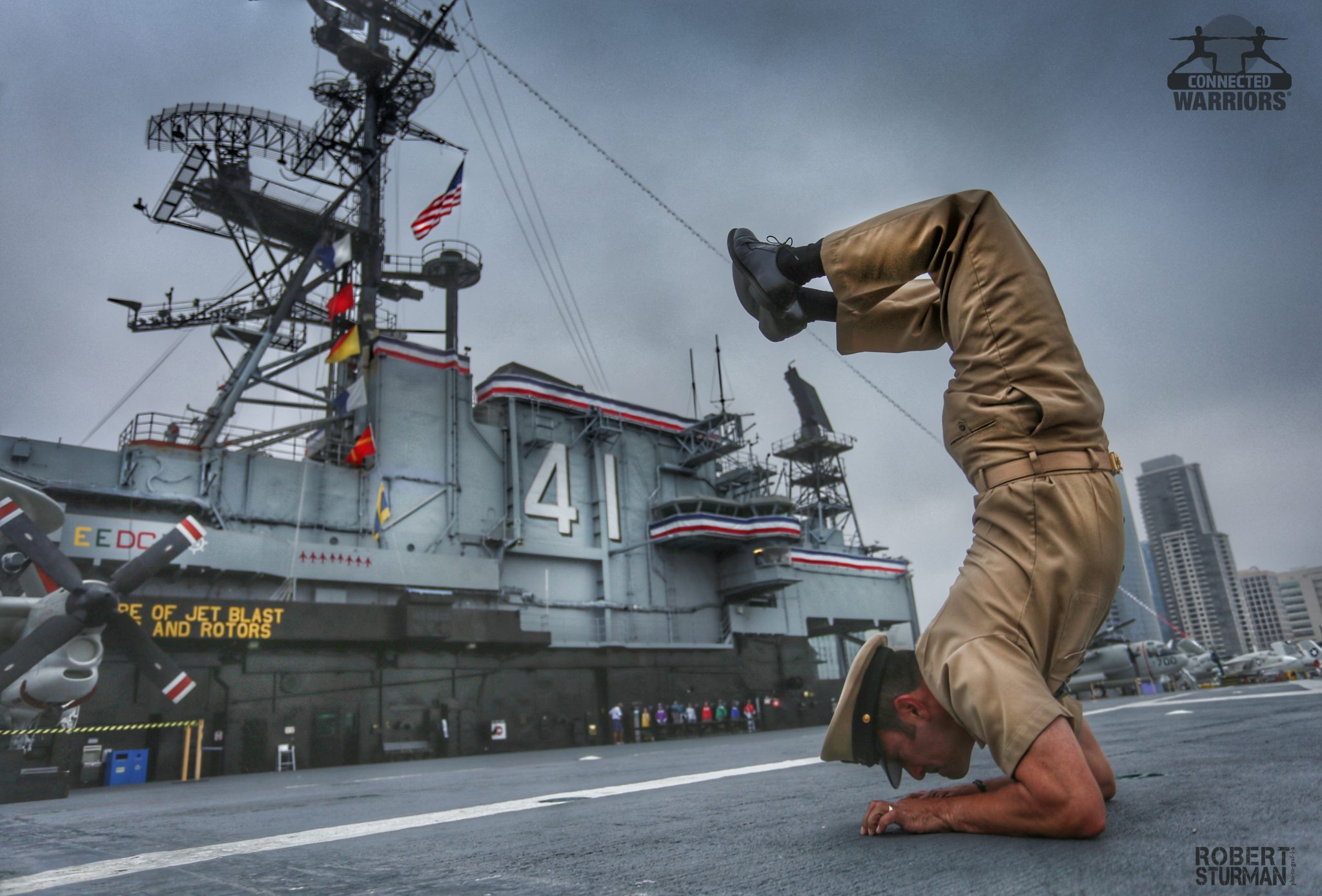navy soldier in scorpion pose by boat