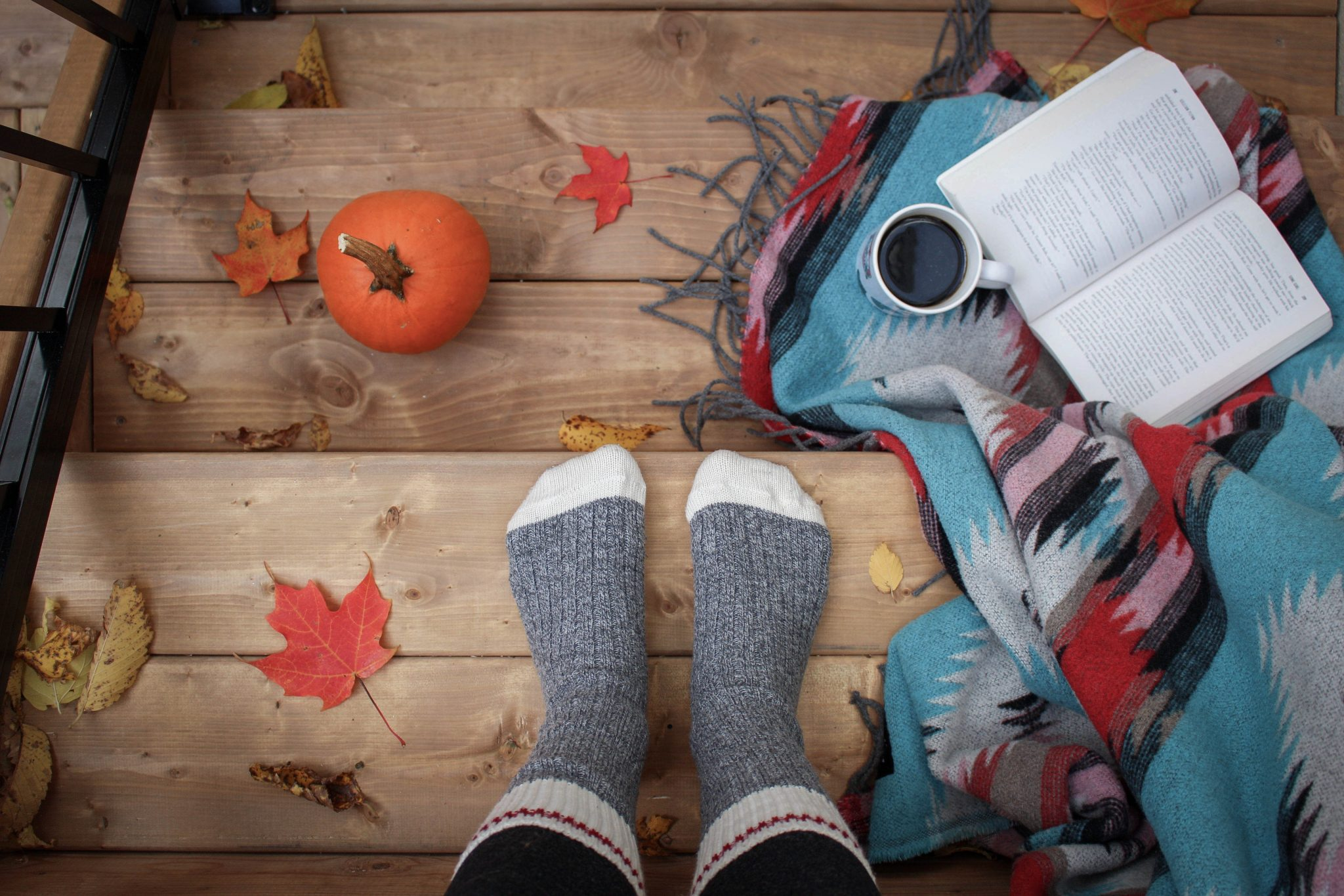pumpkin on stars with feet and open book, cup of coffee
