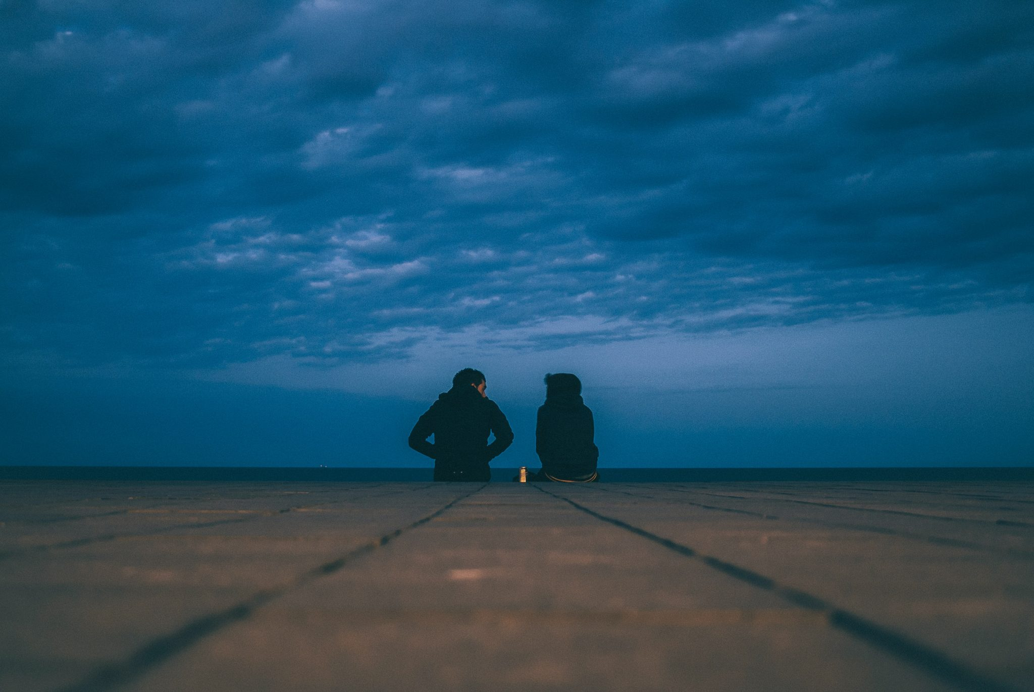 two people at end of pier having tough conversations